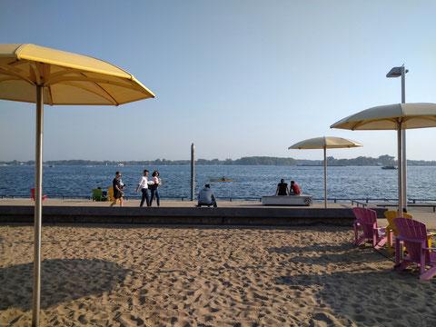「オンタリオ湖の湖岸でくつろぐ人々。天気が良ければカヌーやボートなどもたくさん出てます」