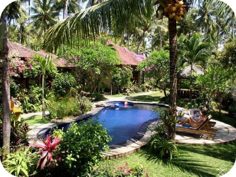 in the tropical natural garden, pool, bungalows hidden behind the beautiful flowers, bushes and trees