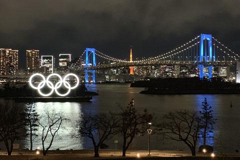 東京タワーと夜景を背景にしたお台場海浜公園の五輪シンボル