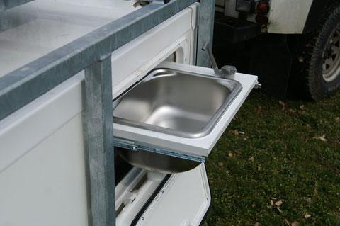 un évier alimenté par une pompe électrique installée dans un réservoir fixe d'eau propre