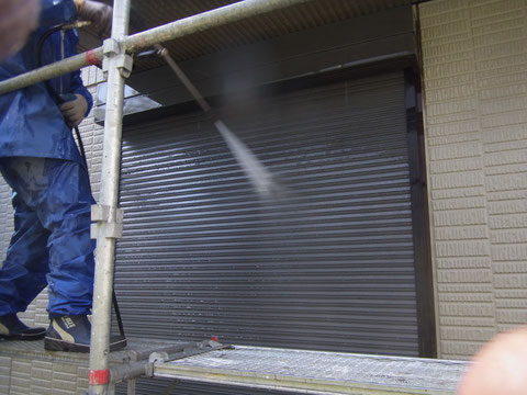 外壁塗装工事において塗装前にシャッターを高圧洗浄しています。
