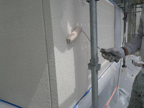 熊本市の外壁塗装時。外壁の中塗りをローラーにて手塗りを行っています。