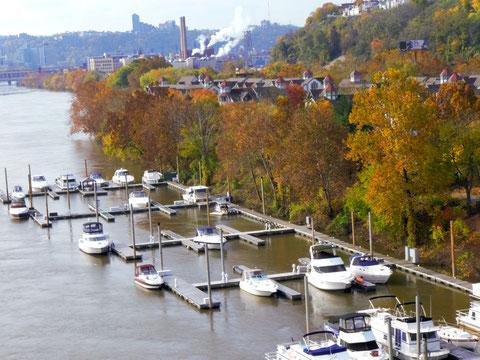 Indian Summer am Allegheny River in Pittsburgh. Die bunten Blätter der Bäume spiegeln sich im Wasser.