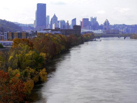 Herbstlich bunte Laubfärbung des Indian Summers am Allegheny River. Im Hintergrund ist das Stadtzentrum Pittsburghs zu sehen.