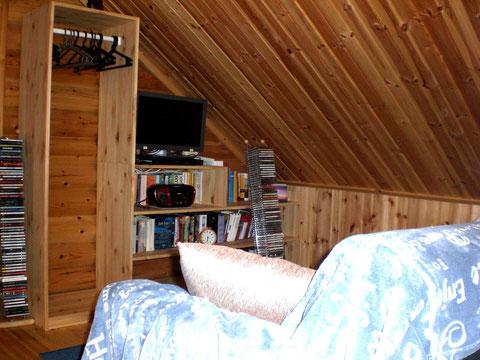 Lese- und Multimediaecke mit gemütlichem Sofa und Leselampe.