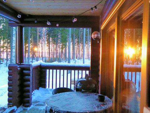 Die Wintersonne schickt die letzten Strahlen ins Mökki. Jetzt den Kaminofen anfeueren und mit einem finnischen Glögi davor träumen.