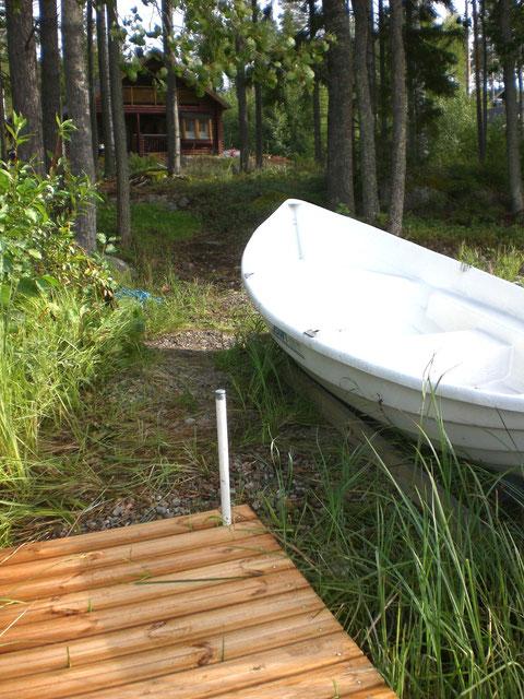 Blick von der Badestelle mit Steg und Boot. Im Hintergrund das Ferienhaus (50m).