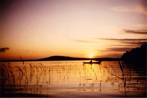"""Genießen Sie entspanntes Angeln im eigenen Boot bei Sonnenaufgang in  den Schilfzonen der Bucht vor dem Haus. Im Hintergrund der 1,5 km vom Haus entfernte """"Berg"""" mit Aussichtsturm der Insel Päijätsalo bei Sonnenaufgang."""