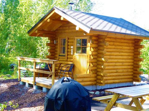 Traditionelle holzbefeuerte Blockhaus-Außensauna direkt am Haus. 50 m zum See. Abendsonne und Blick aus der Sauna auf den See. Holzofen mit Glastür und 200 kg Steinen. Blick aus der Sauna in die Abendsonne und den See.