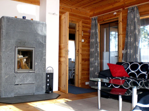 Massiver Speckstein-Kaminofen, 2.000 kg im großzügigen, hellen Wohnzimmer mit Seeblick.