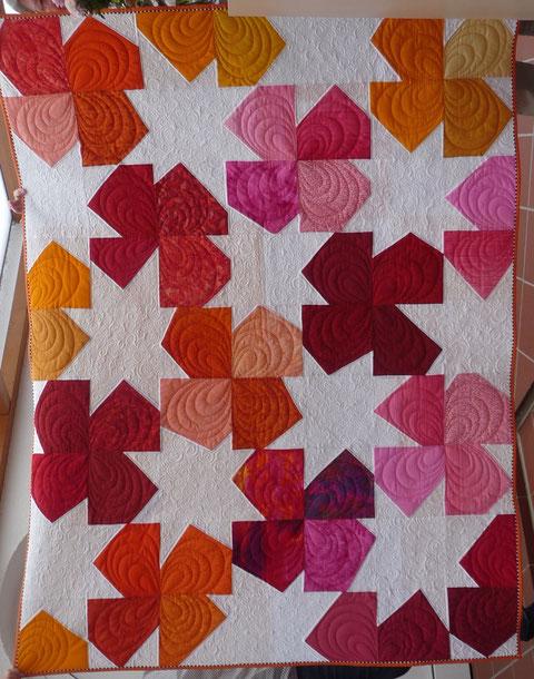 Verlosungsquilt.  Gequiltet von Patricia Bussemeier.  Das Muster heißt Starflower.
