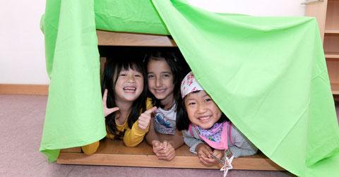 Kinder bauen sich eine Höhle.
