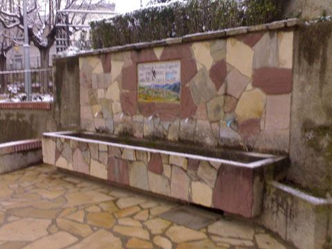 Fuente natural,el parque infantil al fondo.