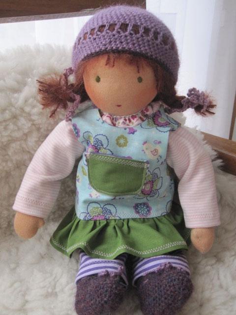 Fridas Puppe hat rotbraune Mohair-Schurwoll-Haare und olivgrüne Augen. Bekleidet ist sie mit Shirt und Leggings aus Ringeljersey, Schürzenkleidchen mit Rüsche und Tasche, Häkelmütze und -schühchen aus Alpaka-Seiden-Garn