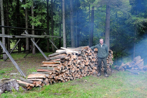 Der junge Mann ist über 1,90 groß, das zeigt die Größe des Holzstapels.