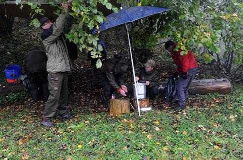 Mit einer Zeltbahn und einem Schirm versuchen zwei unserer Freunde uns eine angenehme Mittagspause zu gestalten.