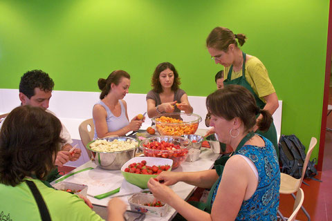 Viele Hände schnippeln Erdbeeren, Bananen und Aprikosen.