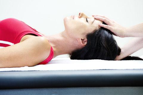 Osteopathiebehandlung am Kopf mit weiblicher Patientin