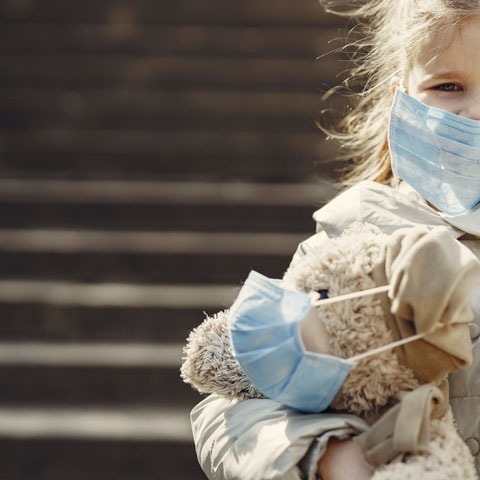 Kind mit Maske und Kuscheltier