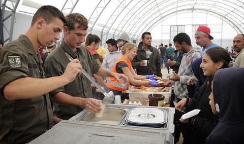 Zwei Pioniere geben Flüchtlingskindern Essen aus der Feldküche