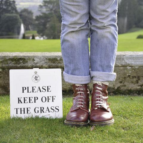Person mit Schuhen auf Gras, daneben ein Schild: Please Keep Off The Grass