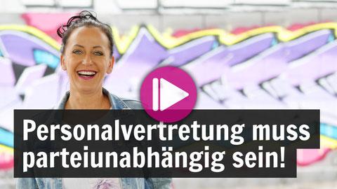 Sandra Gaupmann vor einem Graffiti, sie lacht in die Kamera