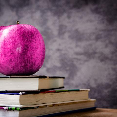 Lehrertisch mit Apfel und einem Bücherstapel