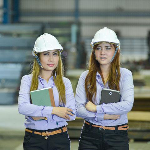 Zwei asiatische Arbeiterinnen mit Helm