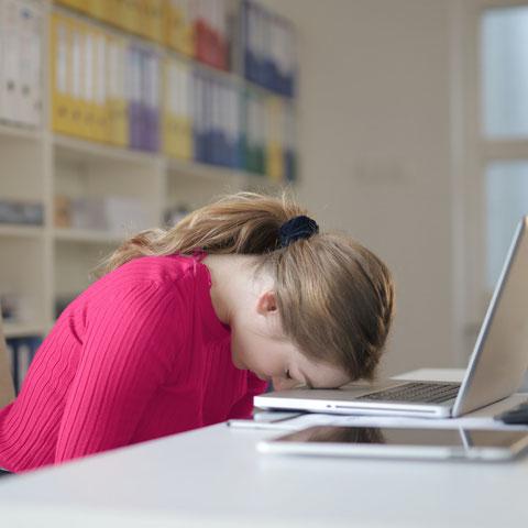Frau legt ihren Kopf auf die Tastatur ihres Computers