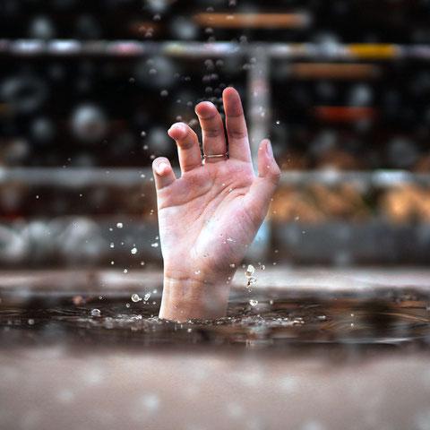 Die Hand eines Ertrinkenden im Wasser