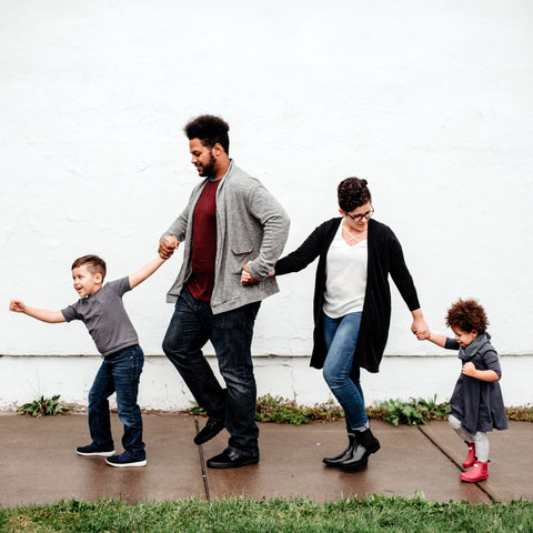 Zwei Kinder mit ihren Eltern Hand in Hand
