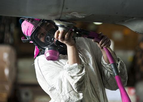 Bild: Eine Leiharbeiterin bei Arbeiten an der Tragfläche eines Passagierjets