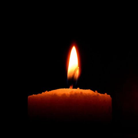 Eine Kerze brennt im Dunkeln