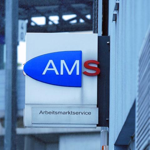 AMS-Schild an einer Hausfassade