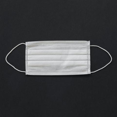 Papiermaske vor schwarzem Hintergrund