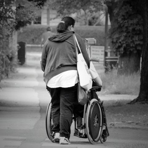 Schwarz-Weiß: junge Frau schiebt einen Rollstuhl - von hinten zu sehen
