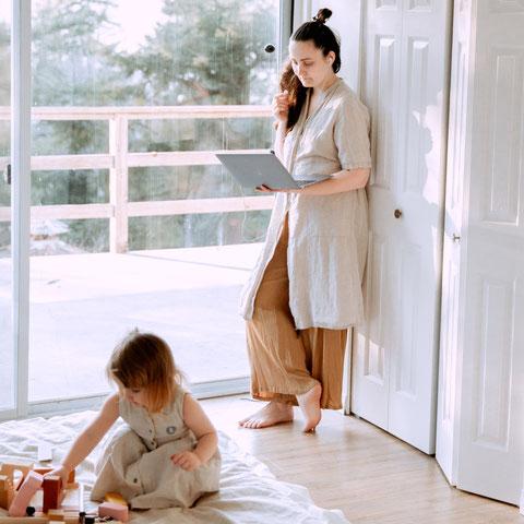 Mutter mit Notebook steht neben spielender Tochter