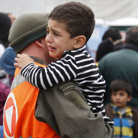 Ein österreichischer Soldat trägt ein weinendes Flüchtlingskind