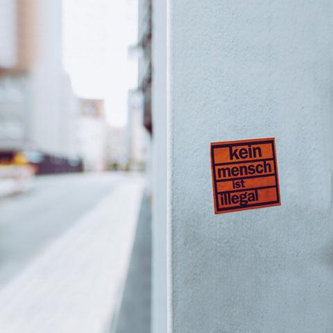 Aufkleber an einer Hauswand: Kein Mensch ist illegal