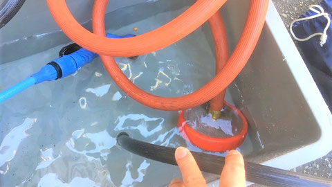 給水ホース(オレンジ)、余水ホース(黒)の先端をコンテナ水中に沈める