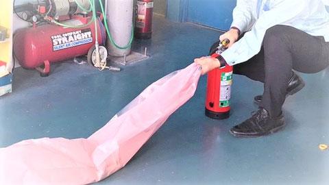 消火器を噴射するとピンク色の粉