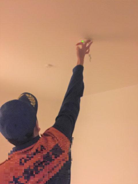 天井の住警器を試験する予防担当者