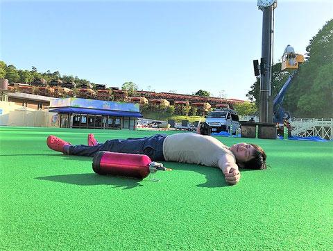 プールサイドの人工芝で消火器(みほん)と昼寝