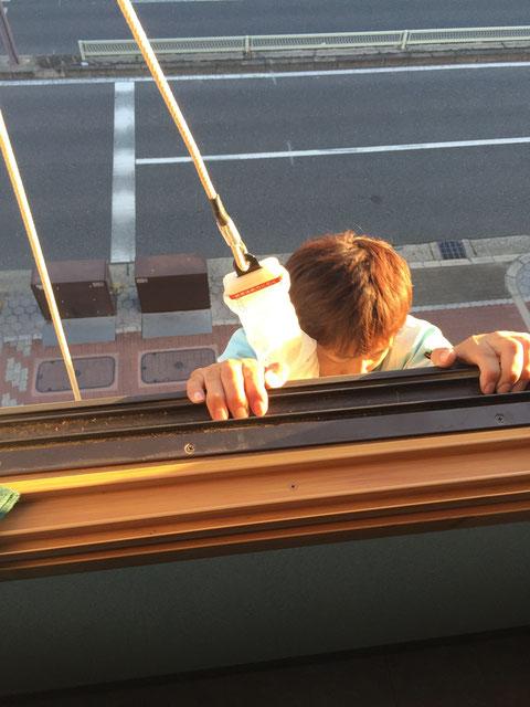 建物を正面に窓外に身体を出す