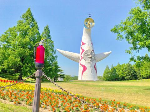 太陽の塔の赤色とマッチする消火器(みほん)