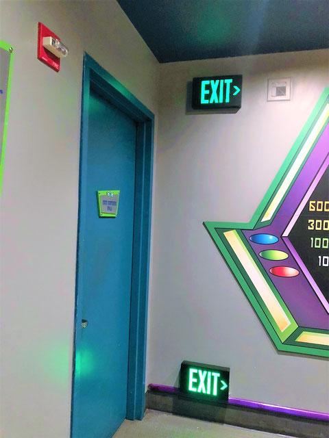 「EXIT >」とあるので青いドアは避難口では無い