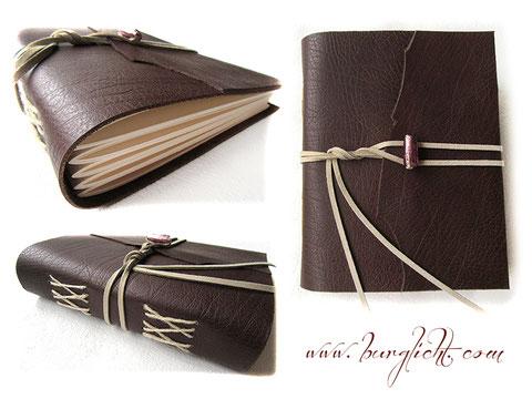 Lederbuch - EchtLeder Softcover mit Kreuzstichbindung, umlaufender Lederkordel und Glasrechteck als Buchverschluss.