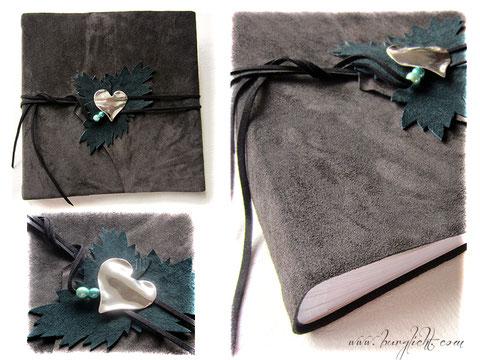 Fotoalbum aus dunkelbraunem Leder mit dunkelgrünen Lederblättern und antikplatinfarbenem Herzanhänger.