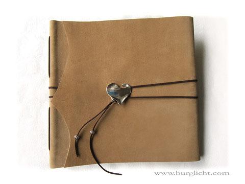 Lederalbum Softcover, Leder rau natur sandfarben, dunkelbraune Lederbändern, großer altplatinfarbener Herzanhänger, 100 Seiten weiß mit Pergamin.