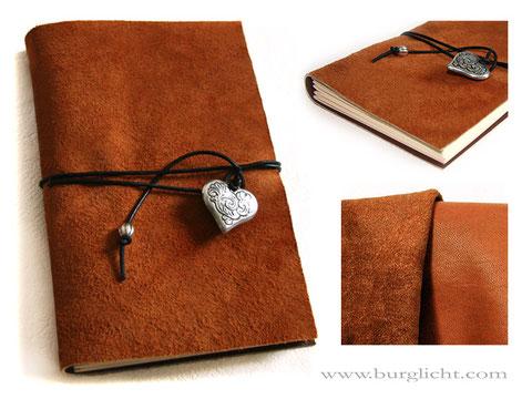 Ledertagebuch, A5 Format, Softcover, Leder dunkelcognacfarben, raue Lederseite außen, umlaufender Buchverschluss mit Herzanhänger